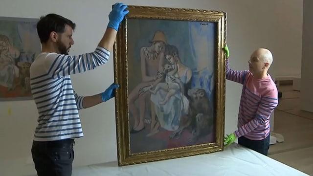 Zwei Männer mit Handschuhen halten ein Gemälde