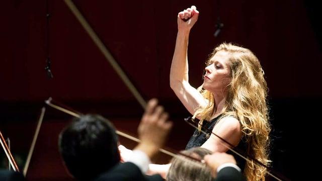 Frau vor Geigenspielern hält die Faust in die Höhe.