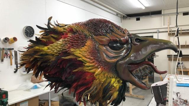 Eine fertige Vogelmaske mit rot-gelben Federn.