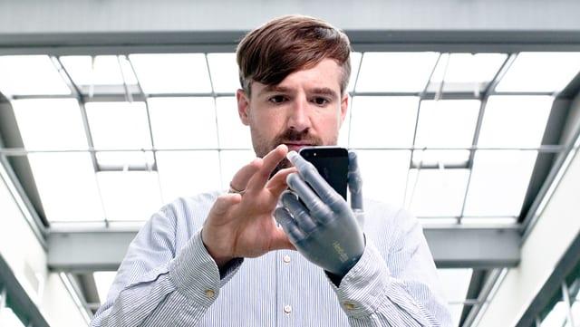 Bertolt Meyer hält ein Smartphone mit seiner Prothese und tippt mit der anderen Hand.