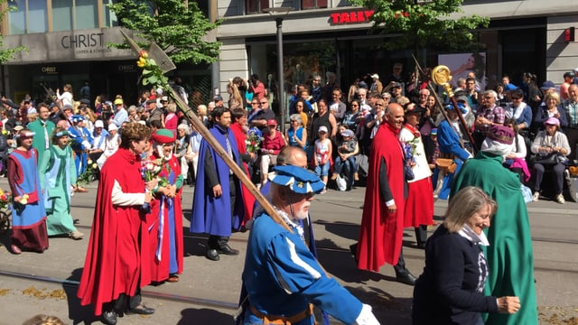 Menschen in roten Kostüme und blauen Trachten