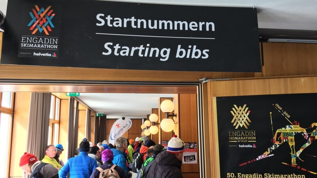 Purtret da persunas che stattan en colonna. Sura penda in banner cun scrit si «Startnummern/Starting bibs».