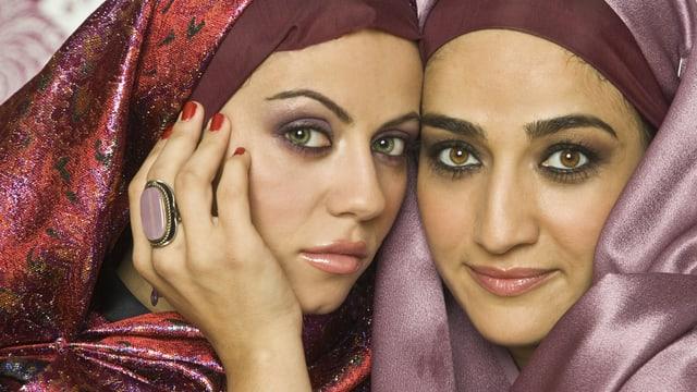 Zwei muslimische Frauen. Sie tragen Kopftuch und sind stark geschminkt.