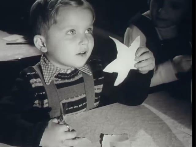 Ein blonder Junge schneidet Papiersterne aus.
