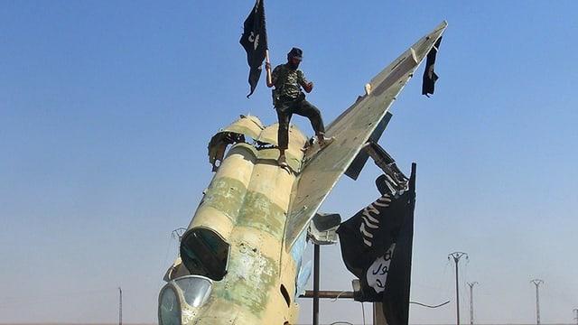 Ein Mann mit einem eurpäisch anmutenden Hut hisst eine IS-Fahne auf einem eroberten Flugzeug.