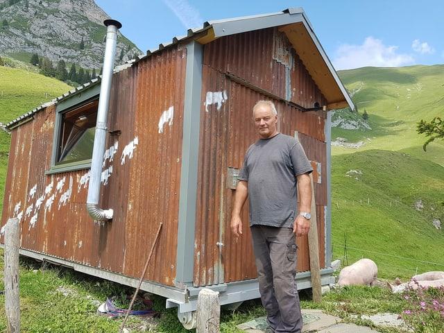 Eine Mann vor einer kleinen Berghütte.
