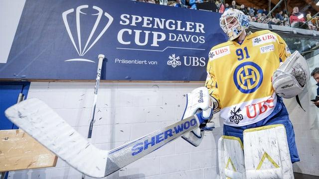 Purtret d'in giugader dal HCD davant il logo da la Cuppa Spengler.
