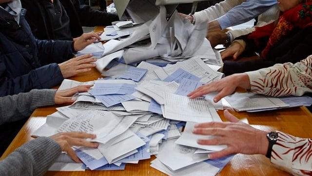 Ein Tisch voll mit Wahllisten und Hände, die nach ihnen greifen.