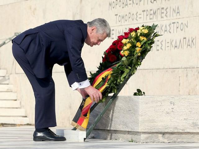 Ein Mann im dunklen Anzug legt einen grossen Blumenkranz nieder.