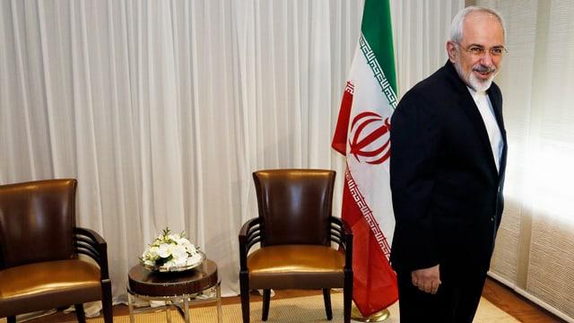 Irans Aussenminister Sarif stehend vor zwei Sesseln und einer iranischen Fahne.