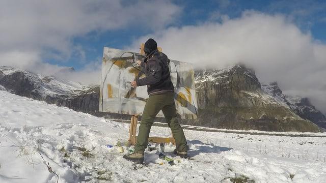 Eine Künstlerin malt im Schnee.