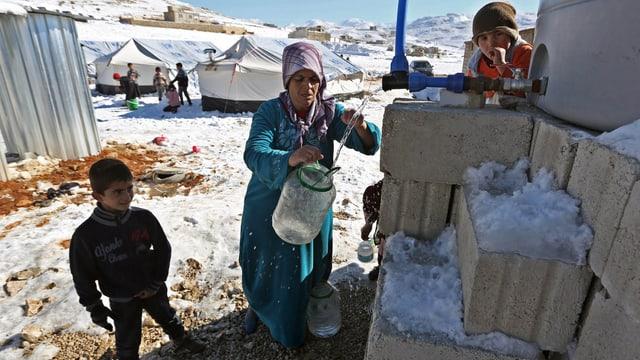 Eine Frau füllt Wasser in einen Behälter in einem Flüchtlingslager, der Boden ist schneebedeckt.