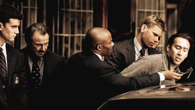 Ein Mann beugt sich über ein Auto - er wird von 4 anderen Männern festgehalten