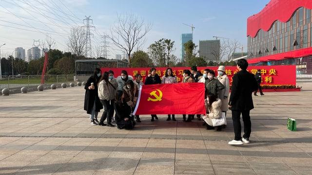 Studentinnen und Studenten posieren vor Covid-Ausstellung.