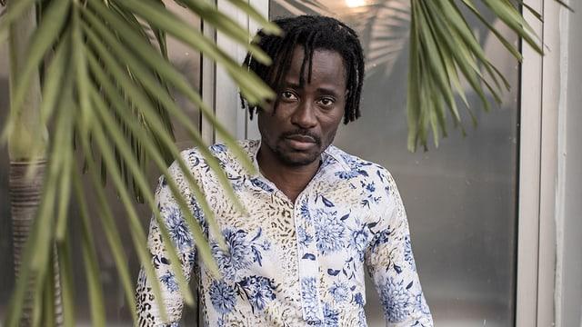Bisi Alimi trägt ein blau-weisses Hemd. Er steht hinter einem Palmwedel.