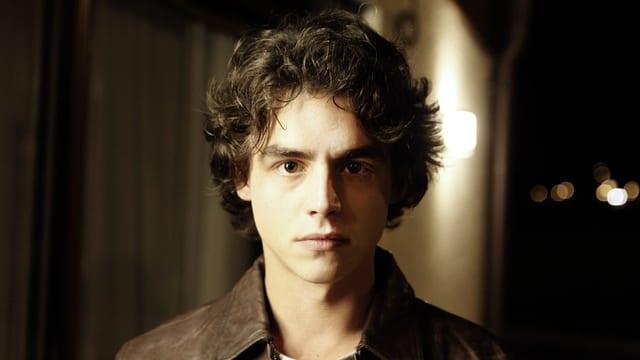 Ein Mann mit dunkeln Haaren und braunern Lederjacke schaut eindringlich in die Kamera.