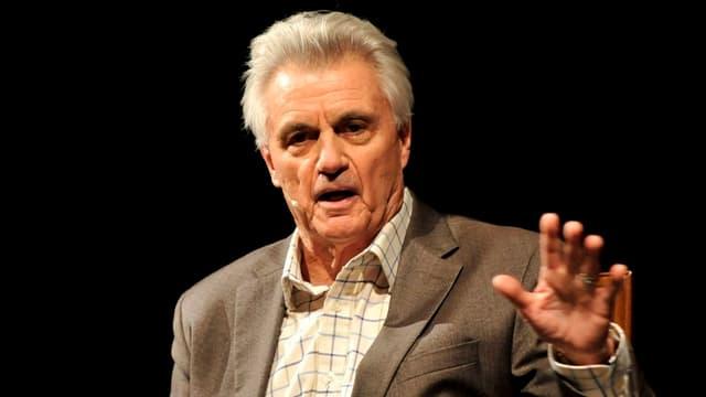 Nahaufnahme von Autor John Irving: Der grauhaarige Mann spricht auf einer Bühne.