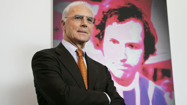 Franz Beckenbauer posiert vor einem Gemälde mit seinem Konterfei.
