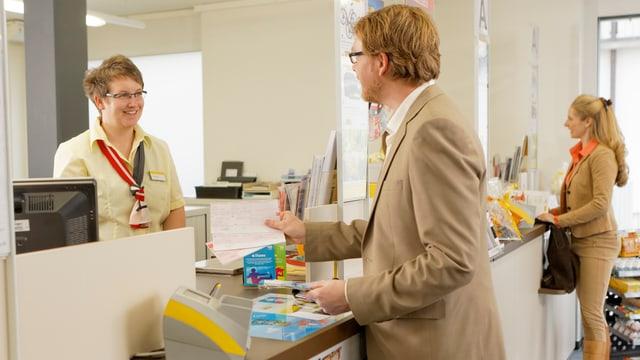 Symbolbild: Mann am Postschalter mit einer Rechnung in der Hand, hinter dem Schalter eine Postangestellte.