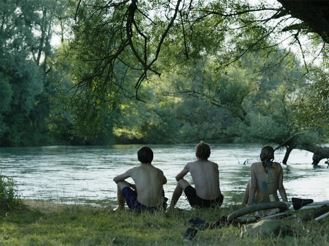 Drei Jugendliche sitzen am Flussufer und schauen zum Wasser.