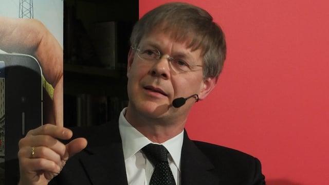 Gerhard Schafroth argumentiert auf einem Wahlpodium und deutet mit Daumen und Zeigfinder eine Distanz an.