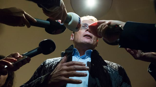 Roger Köppel vor vielen Mikrofonen.