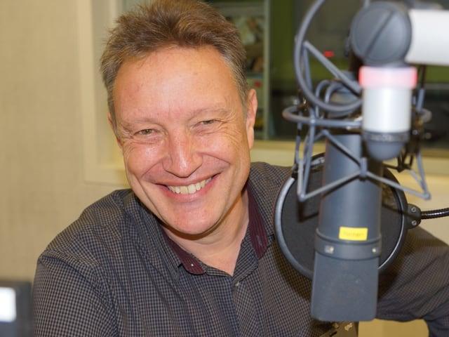 Ein lachender Mann vor einem Mikrofon.