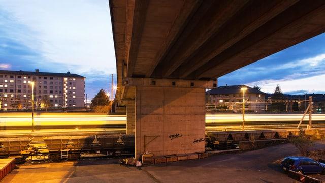Ein durchfahrender Zug in der Dämmerung, darüber eine Brücke.