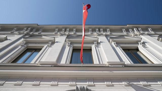 Gebäude des Bundesstrafgerichts fotografiert von unten, darauf auch eine Schweizerfahne, die über dem Eingang hängt.