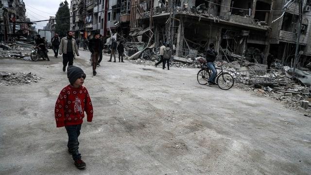 Menschen auf der Strasse. Im Hintergrund zerbombte Gebäude.