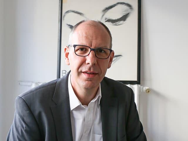 Charles Liebherr vor einem Bild im Hintergrund.