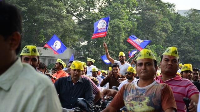 Männer mit gelben Käpchen und Flaggen protestieren.