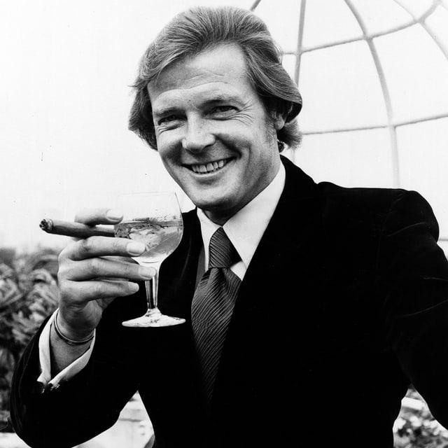 Roger Moore mit Zigarre und Weinglase (1972)