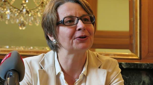 Portrait von Martina Bernasconi, die zu einem Publikum redet, das man nicht sieht. Vor ihr ist ein Mikrophon.