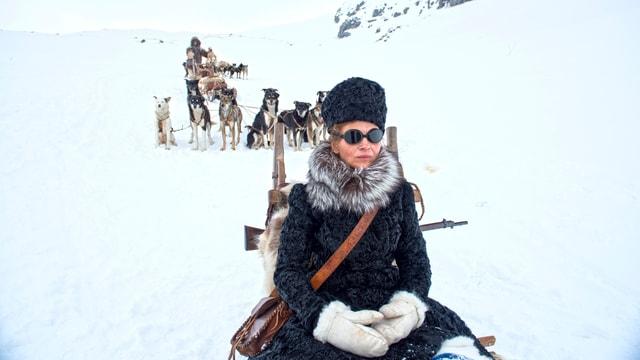 Juliette Binoch in einer Schneelandschaft. Sie trägt einen Pelzmantel und sitzt auf einem Schlitten. Hinter ihr sind Hunde.