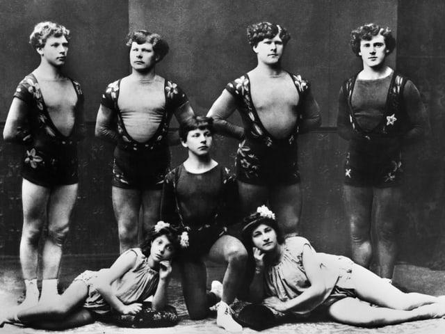 Auf einer alten Aufnahme stehen mehrere junge Männer in Kostümen in einer Reihe.