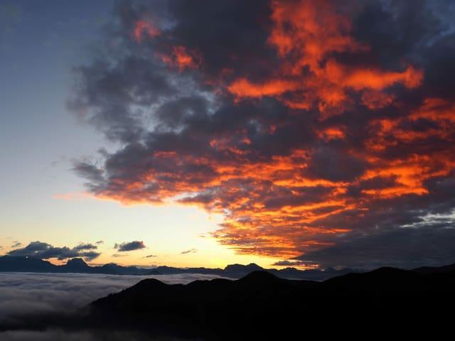 Die Sonne lässt Wolkenfelder rot erscheinen. Blick von Berg, im Tal Hochnebel.
