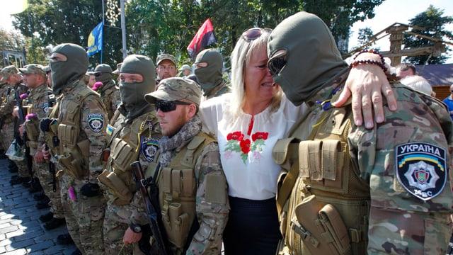 Soldaten stehen in einer Reihe, neben einem steht eine weinende Frau, seine Mutter.