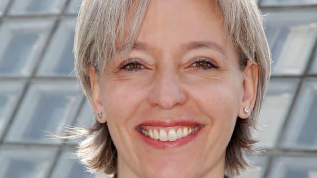 Brigitte Hollinger lächelt in die Kamera, sie trägt Seitenscheitel, hat halblange graue Haare.