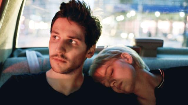 Ein Mann und eine Frau im Auto. Sie schläft auf seiner Schulter.