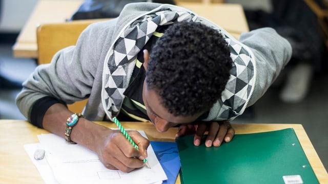 Junger Mann beugt sich über Aufgabenblatt.