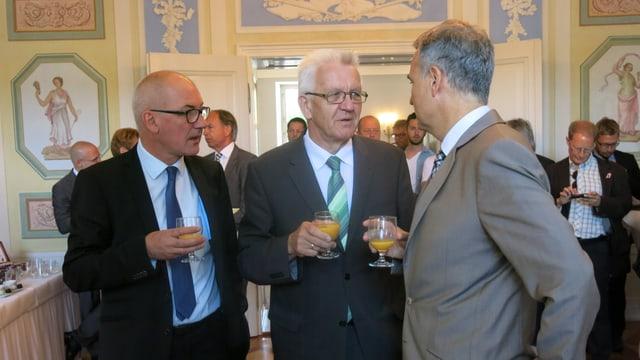Drei Männer reden miteinander, haben alle Orangensaft in der Hand