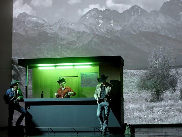 Zwei Cowboys an einer grün beleuchteten Bar.