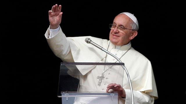 Papst Franziskus winkt vor schwarzem Hintergrund der Menge zu.