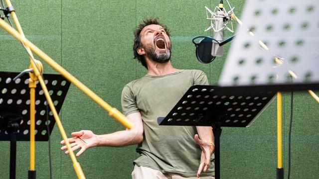 EIn Mann in einem Tonstudio, mit weit aufgerissenem Mund