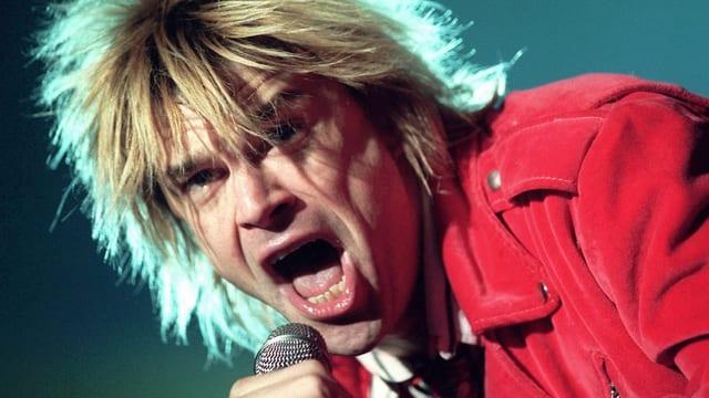 Campino mit einer blonden Mähne und einer roten Jacke. Er singt.