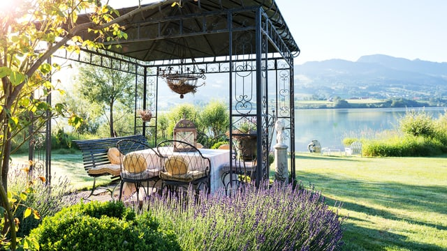 Ein Pavillon aus Stahl, darin ein Tisch mit Stühlen und eine rBank, rundherum Gartem, am Horizont ein See.