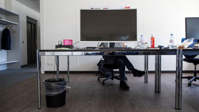 Ein Mann sitzt hinter einem Bildschirm und arbeitet.