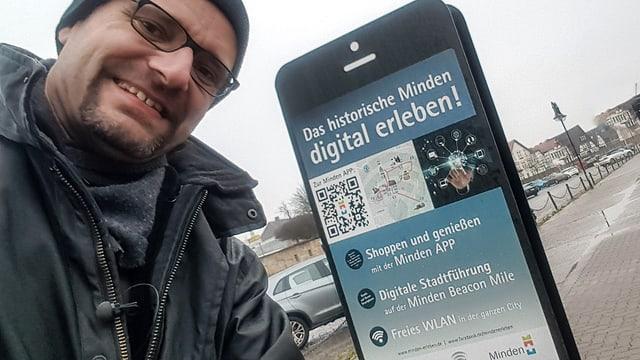 Digitalredaktor Reto Widmer neben einem mannshohen Smartphone in Minden.