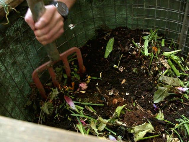 Kompost wird mit Gabel gemischt